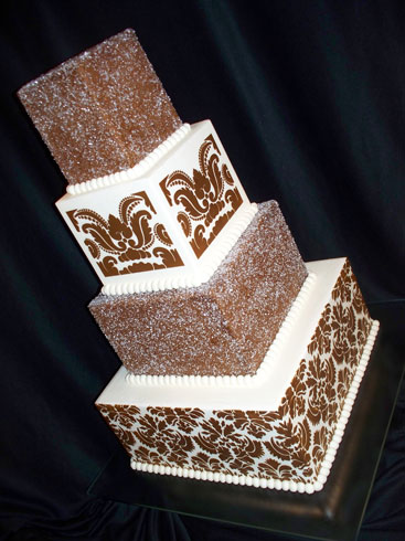 "This is a 12"" chocolate rush cake filled with red raspberry. An 8"", 6"" & 4"" butter pecan cake, one filled with apple and one with lemon, no filling in the top tier. Creme de cacao butter cream over all. Brown damask stencilling and 2 tiers sugar coated. Served 130. Reception was held at the Metropolitan Center in downtown Canton."
