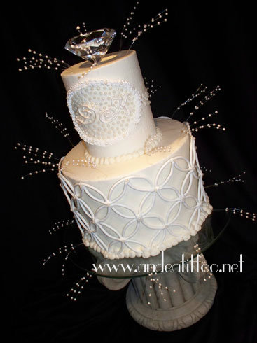 "Engagement! This is an 8"" & 4"" golden cake, frosted & filled with creme de cacao butter cream. Royal icing decorations with a real diamond (yeah right) on top. Served 32. The whole proposal and party were a surprise, apparently she accepted and all is well in their world. www.andeatittoo.net"