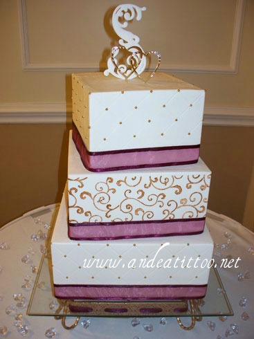 "Gold Scrolls & Quilt. 12"" & 8"" almond cake, 10"" orange cake, all filled with raspberry. Amaretto butter cream over all. Real ribbon. Served 154. Reception was held at Courtyard Marriott in Canton."