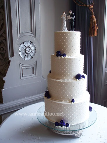 "First wedding cake of the season! This is a 12, 8 & 6"" almond cake and a 10"" chocolate rush cake. 10 & 8"" are red raspberry filled, the other 2 are torted & butter cream filled. Creme de cacoa butter cream over all & filling in 12 & 6"". Roses are purple butter cream. Wedding and reception were held at the Tudor Arms Hotel in Cleveland. Served 130."