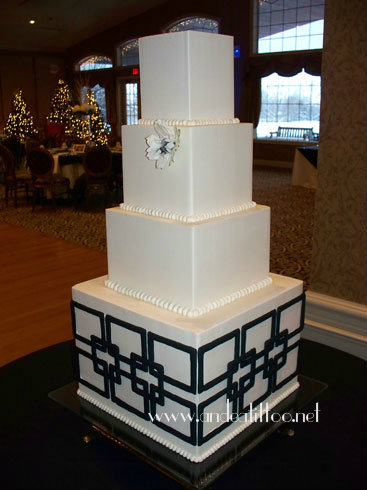 "Hillary's Cake! This was a 12"", 8"", 6"" and 4"", all cinnamon cake, torted, filled & frosted with cinnamon butter cream. The bottom tier was 9.5"" tall, was actually 1.5 tiers. The black design was royal icing. The flower was silk. Cake fed Served 166 as shown. The reception was held at Weymouth Country Club in Medina."