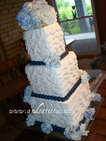 """Waves"" 8"" vanilla cake filled with raspberry cream cheese, 6"" & 4"" butter pecan cake torted & filled eith butter cream. Creme de cacao butter cream over all. Fresh flowers. Served 58. Wedding & reception held on Mohawk Lake in Malvern."